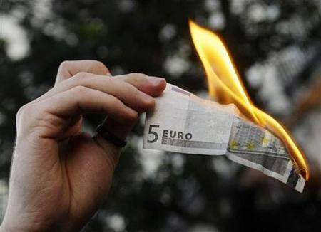 A demonstrator burns a five euro note during a protest in downtown Madrid against capitalism and the G20 Summit on Financial Markets and the World Economy November 15, 2008. REUTERS/Susana Vera