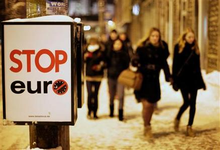 People walk past a placard placed by anti-Euro activists in Tallinn December 31, 2010. Estonia will join the euro zone from January 1, 2011. REUTERS/Ints Kalnins