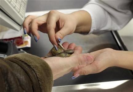 A cashier gives change to a customer in Euro coins in a supermarket in Tallinn January 1, 2011. REUTERS/Ints Kalnins
