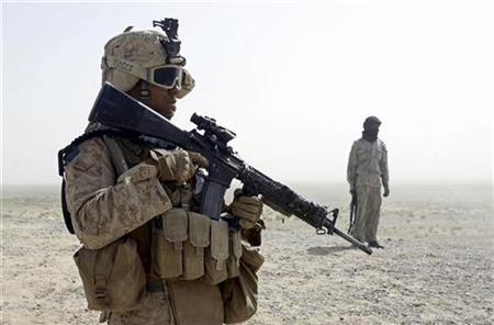 A U.S. Marine patrols with a member of an Afghan border guard unit in the desert of the lower Helmand River valley, in southern Afghanistan in this July 1, 2009 file photo. REUTERS/ Peter Graff