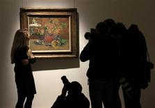 "<p>An employee poses for photographers in front of artist Paul Gaugin's ""Sunflower"" at Christie's auction house in London January 7, 2011. Christie's pre-sale estimate for the 46 lots of its impressionist and modern art sale on February 9, 2011 is from $114,630,000 to $169,216,000. REUTERS/Stefan Wermuth</p>"
