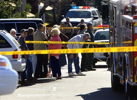 People and law enforcement personnel stand at a parking lot where U.S Representative Gabrielle Giffords (D-AZ) was shot along with others at a Safeway in Tucson, Arizona January 8, 2011. REUTERS/Eric Thayer