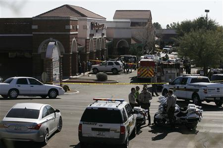 Law enforcement personnel work a crime scene where U.S Representative Gabrielle Giffords (D-AZ) was shot along with others at a Safeway in Tucson, Arizona January 8, 2011. REUTERS/Eric Thayer