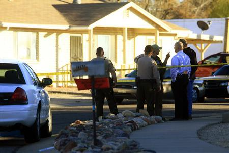 Law enforcement personnel stand outside the home of Jared L. Loughner, identified by federal officials as the suspect responsible for the shooting of U.S Representative Gabrielle Giffords (D-AZ), in Tucson, Arizona January 8, 2011. REUTERS/Eric Thayer