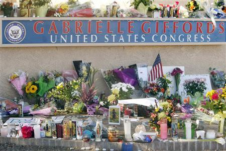 The memorial set up containing candles, flowers and stuffed animals is seen outside the offices of congresswoman Gabrielle Giffords in Tucson, Arizona January 9, 2011. REUTERS/Rick Wilking