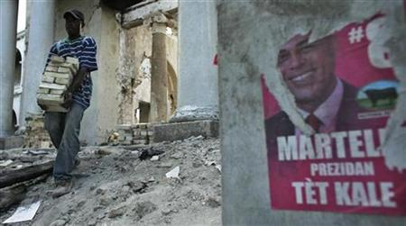 A man collects bricks stolen from the Ministry of Finance building which was destroyed during the January 2010 earthquake, as he walks near a poster of Haiti's presidential candidate Michel Martelly in Port-au-Prince January 6, 2011. REUTERS/Eduardo Munoz