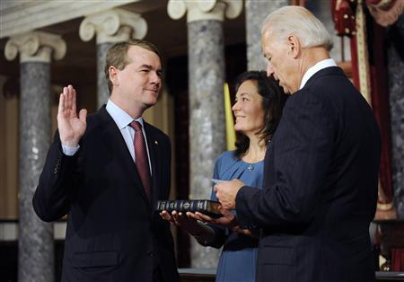 U.S. Senator Michael Bennet during his swearing-in by Vice President Joe Biden in the Old Senate Chamber, January 5, 2011. Federal prosecutors have charged a Colorado man with threatening gun violence and arson against staff of Bennet. His wife Susan Daggett is seen next to him. REUTERS/Jonathan Ernst