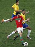 <p>Игрок сборной Португалии Тьягу (слева) борется за мяч с игроками сборной Бразилии во время матча в Дурбане 25 июня 2010 года. Португальский полузащитник Тьягу решил завершить выступления за национальную сборную, сообщила в понедельник Португальская футбольная федерация (FPF). REUTERS/Paul Hanna</p>