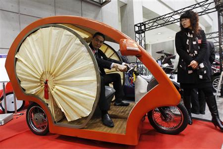 An employee of Japan's Electronic Vehicle maker Yodogawa, poses in its EV (electric vehicle) car ''Meguru'' at the Electronic Automotive Technology Expo in Tokyo January 19, 2011. REUTERS/Kim Kyung-Hoon