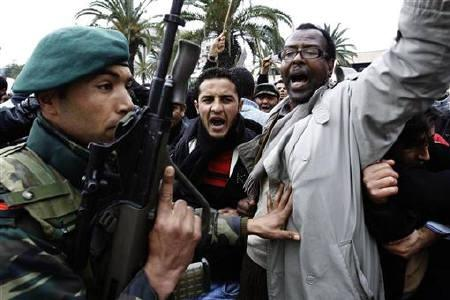 A soldier pushes back a protester as shots are fired in the air in front of the headquarters of the Constitutional Democratic Rally (RCD) party of ousted president Zine al-Abidine Ben Ali during a demonstration in downtown Tunis January 20, 2011. REUTERS/ Finbarr O'Reilly