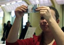 <p>A vendor inspects a 20 Euro bank note in a shopping centre in Tallinn January 1, 2011. REUTERS/Ints Kalnins</p>