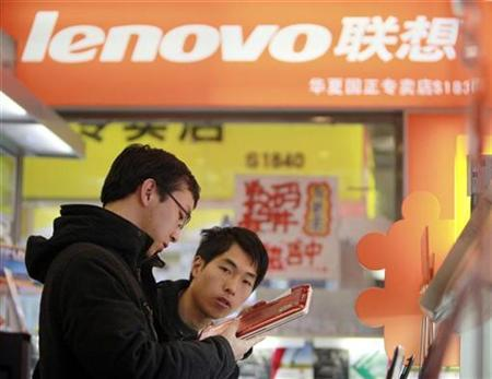 A customer (L) checks a new laptop with a salesman at a Lenovo shop in Beijing December 13, 2010. REUTERS/Christina Hu