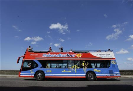 Tourists travel on a double-decker bus for sightseeing on Havana's seafront boulevard 'El Malecon' November 11, 2010. REUTERS/Desmond Boylan (CUBA - Tags: SOCIETY TRAVEL BUSINESS)