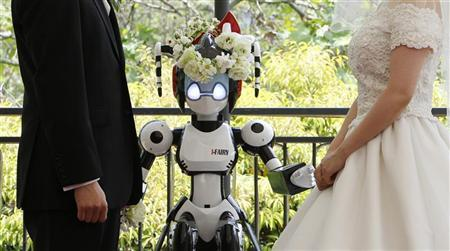 A humanoid robot named ''I-Fairy'' (C) acts as a witness at the wedding ceremony between Tomohiro Shibata (L) and Satoko Inoue in Tokyo May 16, 2010. REUTERS/Yuriko Nakao (JAPAN - Tags: SCI TECH ODDLY SOCIETY)