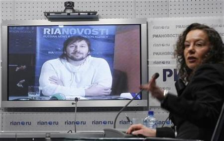 A presenter gestures during a televised news conference with Yevgeny Chichvarkin, a former owner of mobile phone retailer Euroset, in Moscow January 26, 2011. REUTERS/Denis Sinyakov