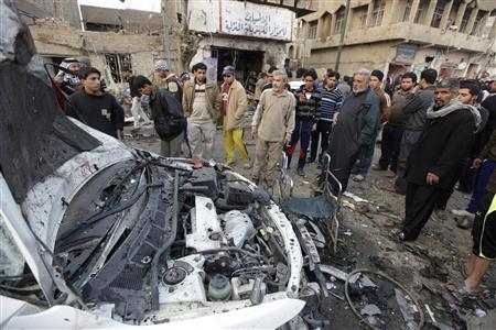 Residents gather at the site of a bomb attack in Baghdad's Shula district January 27, 2011. REUTERS/Saad Shalash