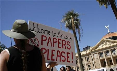A demonstrator holds a sign during an immigration rally outside Arizona's State Capitol in Phoenix, May 1, 2010. REUTERS/Joshua Lott