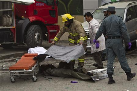 A firefighter puts a scarf over a casualty after a suicide bomb attack at Finest supermarket in Kabul Janury 28, 2011. REUTERS/Ahmad Masood