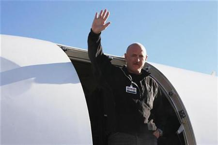 NASA Shuttle Commander Mark Kelly, the husband of U.S. Representative Gabrielle Giffords (D-AZ), waves from a medical transport plane bound for Houston, after his wife was carried aboard in Tucson, Arizona, in this photograph taken and released on January 21, 2011. REUTERS/Office of Rep. Gabrielle Giffords/Jennifer Polixenni Brankin/Handout