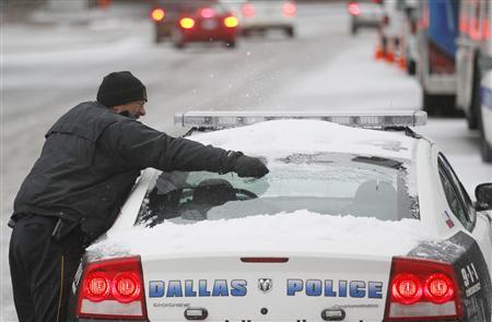 A Dallas police officer removes snow from his car after a storm front moved through Dallas, Texas, February 1, 2011. REUTERS/Jeff Haynes