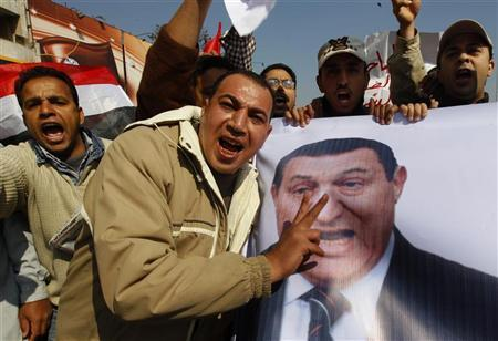 Pro-government Egyptian protesters carry a banner bearing a photo of Egyptian President Hosni Mubarak during a march near Tahrir square in central Cairo February 2, 2011. An Egyptian opposition coalition called on Wednesday for more protests and said it would only negotiate with Vice President Omar Suleiman if Mubarak stepped down. REUTERS/Yannis Behrakis (EGYPT - Tags: CIVIL UNREST POLITICS)