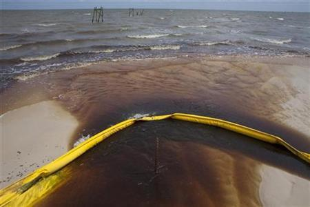 A protective boom is seen as oil from the Deepwater Horizon spill recedes back into the Gulf of Mexico after washing into a drainage canal in Waveland, Mississippi July 7, 2010. REUTERS/Lee Celano