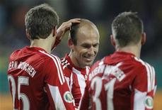 <p>Arjen Robben do Bayern de Munique comemora gol com seus colegas Thomas Mueller (esq) e Bastian Schweinsteiger durante jogo de quartas de final contra o Alemannia Achen. O Bayern de Munique jogará contra a Holanda no próximo ano para compensar os campeões alemães pela perda de Robben após uma lesão que se agravou durante a Copa do Mundo na África do Sul. 26/01/2011 REUTERS/Alex Domanski/Arquivo</p>