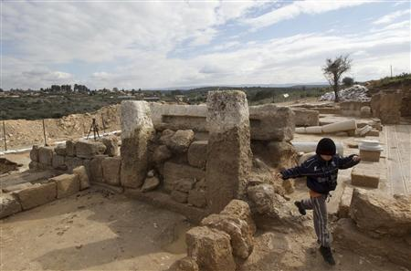 A boy jumps from rocks at the site of an ancient church outside Jerusalem February 2, 2011. REUTERS/Ronen Zvulun