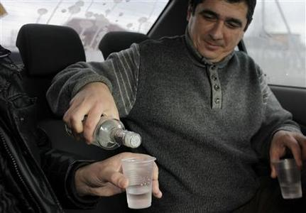 A man fills plastic glasses with vodka to drink it with his acquaintance as they sit in a car in the city of Nazran, January 30, 2011. REUTERS/Diana Markosian