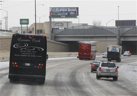 Busses carrying news media are escorted on icy streets to media day for Super Bowl XLV at Cowboys Stadium in Arlington, Texas, February 1, 2011. REUTERS/Brian Snyder