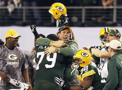 Green Bay Packers head coack Mike McCarthy is hugged by Green Bay Packers defensive tackle Ryan Pickett (79) after defeating the Pittsburgh Steelers in Super Bowl XLV in Arlington, Texas, February 6, 2011. REUTERS/Mike Stone