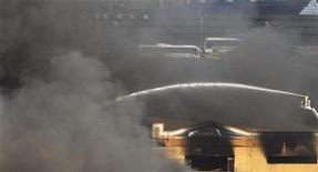 <p>Un grupo de bomberos intenta controlar un incendio entre las bodegas de una escuela de samba en Río de Janeiro, feb 7 2011. Un gran incendio devastó parte del centro de preparativos para el Carnaval de Río de Janeiro, destruyendo cientos de trajes y carrozas alegóricas a menos de un mes del inicio del festival anual de hedonismo en Brasil. REUTERS/Ricardo Moraes</p>