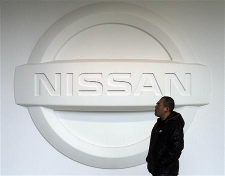 A man walks past a logo of Nissan Motor Co at the company's global headquarters in Yokohama, south of Tokyo February 9, 2011. REUTERS/Toru Hanai
