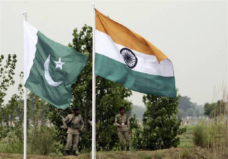 Pakistani rangers stand near the Indian (R) and Pakistani national flags during an annual fair near Pakistan border in Chamliyal, 45 km (28 miles) west of Jammu, June 26, 2008. REUTERS/Amit Gupta
