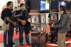 <p>Visitors play Guitar Hero 5 game during the video game show in Paris September 17, 2009. REUTERS/Charles Platiau</p>
