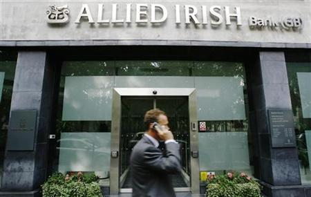 A pedestrian passes a branch of Allied Irish Bank in London August 14, 2009. REUTERS/Luke MacGregor