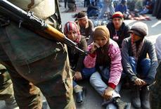 """<p>Демонстранты сидят в военном оцеплении в Каире, 13 февраля 2011 года. Египетские военные, оказавшиеся у власти после ухода в отставку президента Хосни Мубарака, обещают бороться с """"хаосом и беспорядками"""" и готовы начать с запрета на демонстрации. REUTERS/Yannis Behrakis</p>"""