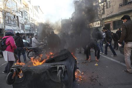 A dumpster burns on a street during clashes between protestors and police near Azadi Square in Tehran February 14, 2011. REUTERS/Your View