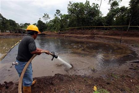 Ecuadorean workers clean up an oil waste pit owned by state petroleum company Petroecuador in Shushufindi, some 410 km (254 mi) east of Quito December 8, 2009.REUTERS/Guillermo Granja