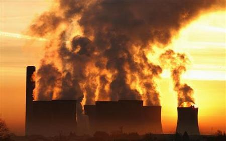 The sun rises behind a coal fired power station in a file photo. REUTERS/Phil Noble
