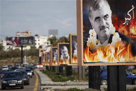 Cars drive past billboards of Lebanon's assassinated former prime minister Rafik al-Hariri at Sidon, southern Lebanon, February 13, 2011. REUTERS/Ali Hashisho