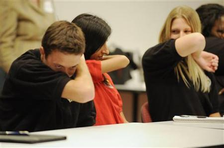 People practice coughing during a meeting for workers at the Maryland Department of Health and Mental Hygiene in Baltimore, September 3, 2009. REUTERS/Jonathan Ernst