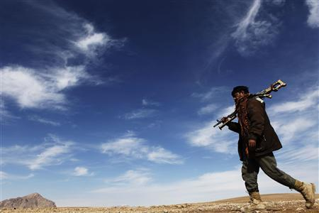 An Afghan policeman carries his weapon during a patrol through Kunjak, southern Afghanistan's Helmand province, February 16, 2011. REUTERS/Finbarr O'Reilly