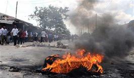 <p>Люди проходят мимо горящей шины в городе Дар-эс-Салам, 1 ноябре 2010 года. Серия взрывов на военной базе в финансовой столице Танзании городе Дар-эс-Саламе унесла жизни по меньшей мере 20 человек, сообщил премьер-министр страны Мизенго Пинда. REUTERS/Emmanuel Kwitema</p>