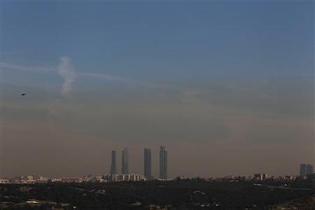 Pollution is seen above Madrid's skyline, including Cuatro Torres business area (C), or Four Towers, in this picture taken from the outskirts of the city February 8, 2011. REUTERS/Susana Vera