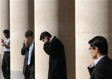 <p>City workers make phone calls outside the London Stock Exchange in Paternoster Square in the City of London at lunchtime October 1, 2008. REUTERS/Toby Melville</p>