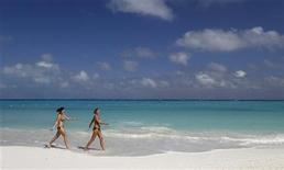 <p>Tourists walk on Caracol beach in Cancun February 1, 2011. REUTERS/Gerardo Garcia</p>