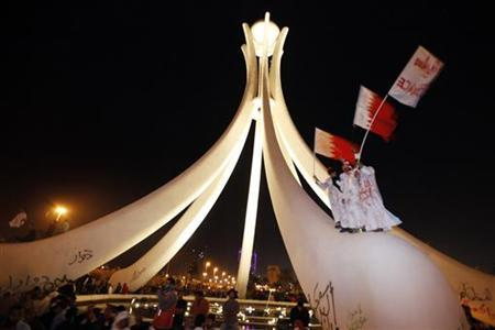 Protesters wave Bahraini national flags after they climb up onto the Pearl Roundabout as they celebrate in Pearl Square in the capital Manama February 19, 2011. REUTERS/Hamad I Mohammed.