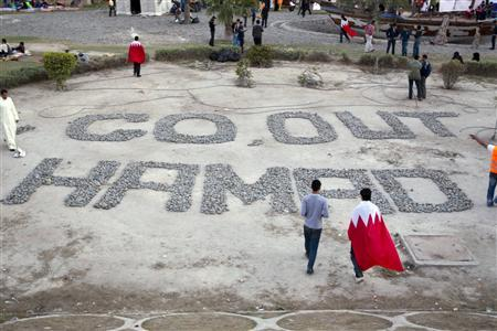 Anti government demonstrators walk around a message written with stones and addressed to King Hamad bin Isa al-Khalifa near Pearl Square in Manama February 20, 2011. REUTERS/Caren Firouz