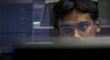 A stockbroker sits in a booth as he looks at the share prices during a trading session inside the trading hall of the Karachi Stock Exchange on February 18, 2011. REUTERS/Athar Hussain